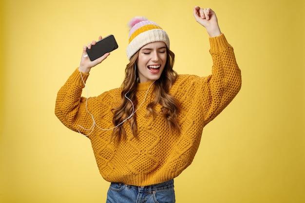 Carefree happy girl enjoying listen music wearing wired earphones raising hands dancing joyfully having fun singing along awesome song playing playlist holding smartphone, standing yellow background