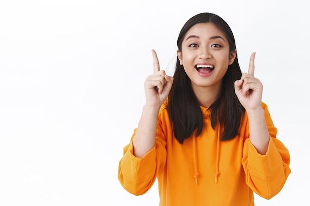ページをクリックする、会社をフォローする、または何かをダウンロードする、指を上に向けてカメラを笑顔にする、オレンジ色のパーカーを着たのんきな幸せな健康なアジアの女の子、製品の購入をお勧めします