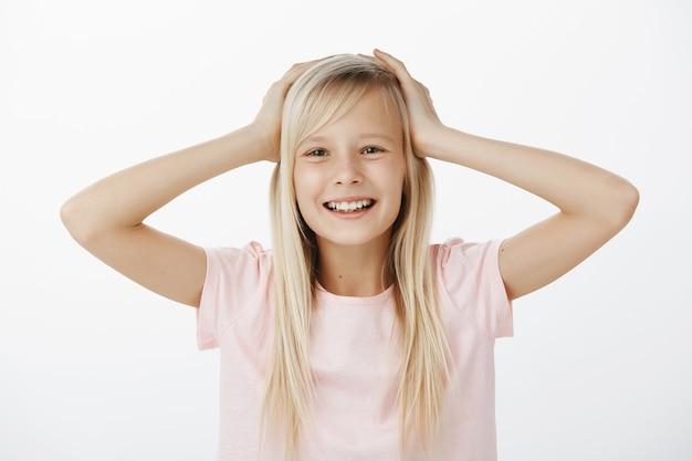 Piccola figlia felice spensierata con i capelli biondi in maglietta rosa, tenendo le mani sulla testa e sorridendo dalla soddisfazione e dall'atteggiamento felice, apprezzando il nuovo gruppo e uscendo con gli amici durante il pranzo