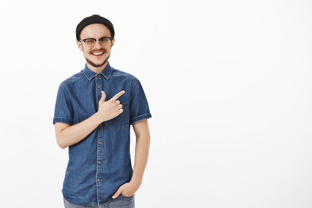 Carefree happy and satisfied handsome male photographer in black trendy beanie and blue shirt pointing at upper right corner smiling broadly with satisfaction and delight