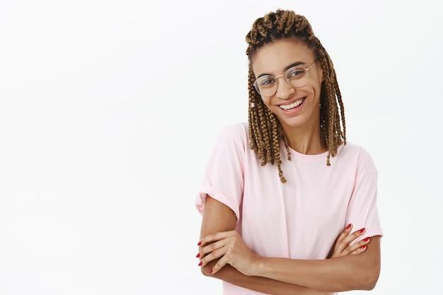 Studentessa afroamericana intelligente felice spensierata in vetri che sembrano contenti