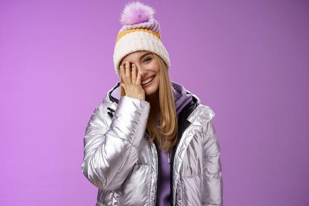 평온한 행복 경쾌한 매력적인 금발 여자 커버 절반 얼굴 기울어 머리를 즐겁게 야외 세련된 실버 재킷 겨울 모자를 쓰고 웃고 재미 멋진 5 성급 스키 리조트, 보라색 배경.