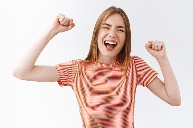 줄무늬 티셔츠를 입은 평온하고 행복한 젊은 활기찬 미녀, 주먹을 쥔 채, 손을 들어 기쁘고 즐겁게 웃고, 격려하고, 자유롭고 쾌활하며, 내기에서 이기고, 챔피언이 된 기분