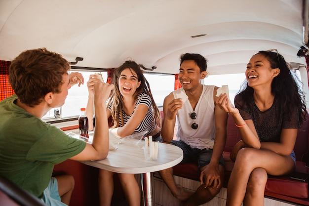 Carefree hipster having fun with cheers inside retro van