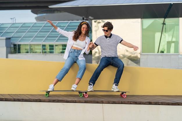 スケートボードの笑いの後に楽しんでいるのんきな流行に敏感な男性と女性の若いカップルは一緒に時間を楽しんでいます