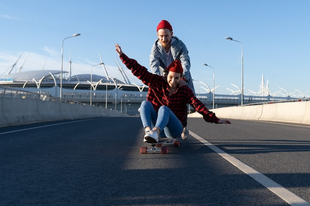 Carefree hipsters couple skateboarding together trendy man and woman enjoy time riding longboard