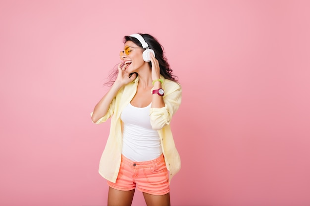 Carefree hispanic woman in pink shorts singing while posing. indoor portrait of fashionable asian girl in white tank-top toucnhing headphones and looking around.