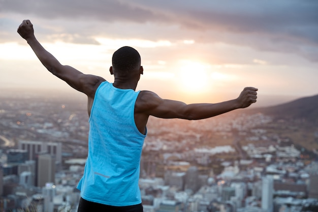 Carefree independent man with dark skin, stands back, stretches hands as holding world, feels freedom, wears blue casual vest, enjoys panoramic view with sunrise. recreation concept