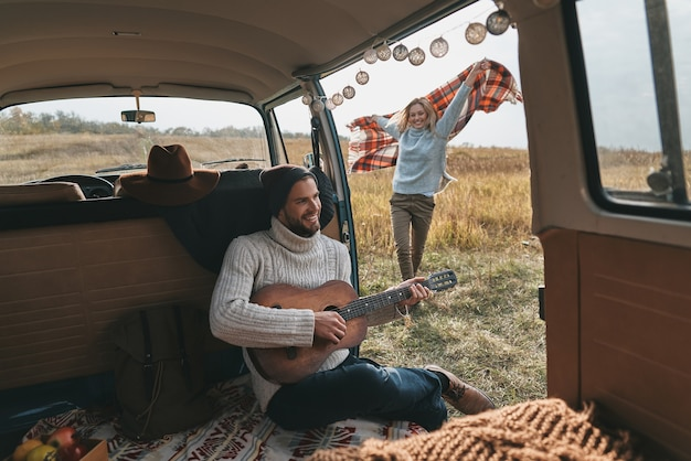 Беззаботное путешествие. красивый молодой человек играет на гитаре для своей красивой подруги, сидя в мини-фургоне в стиле ретро