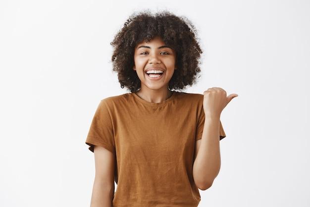 スタイリッシュなtシャツで右を指し、方法を示したり、好奇心旺盛なことについて質問したりしながら笑っている屈託のないうれしそうな、魅力的な若い浅黒い女性