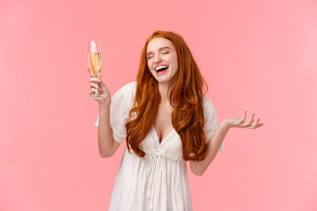 Carefree and joyful attractive redhead female celebrating occasion, having fun on party, close eyes and laughing with raised glass, drink champagne, enjoying awesome company, stand pink