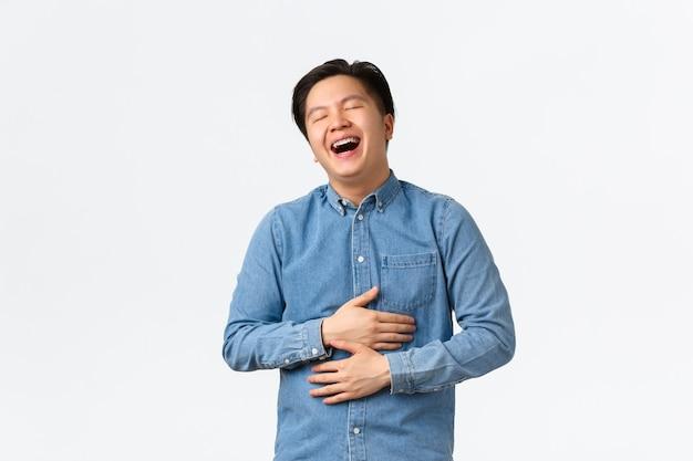 のんきな楽しいハンサムなアジアの男子学生は、楽しんで、コメディを見て、目を閉じて大声で笑っています。男は笑って腹に触れ、陽気な映画、白い背景を楽しんでいます。