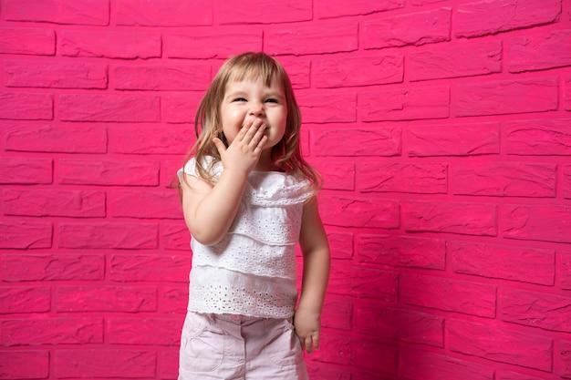 분홍색 표면에 그녀의 손으로 그녀의 입을 덮고 큰 소리로 웃고 평온한 즐거운 어린 소녀.