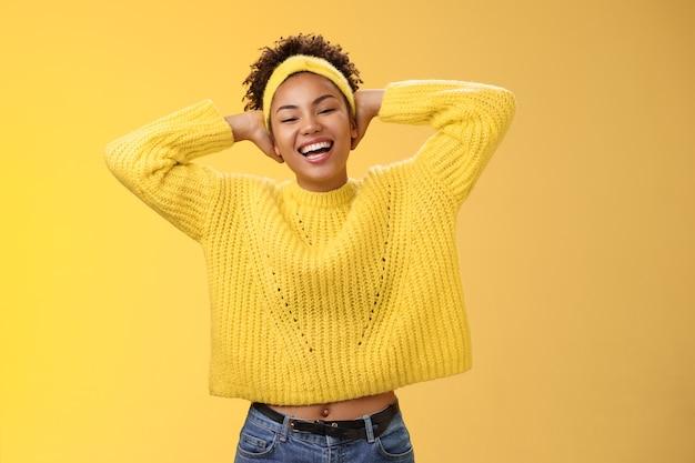 セーターのヘッドバンドでのんきなうれしそうな幸運なアフリカ系アメリカ人の女子学生は、頭の後ろに手を置きます...
