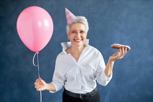 우아한 옷과 eclair와 헬륨 풍선을 들고 분홍색 원뿔 모자를 쓰고 평온한 즐거운 중간 나이 든 여자, 유쾌하게 웃고, 파티에서 재미