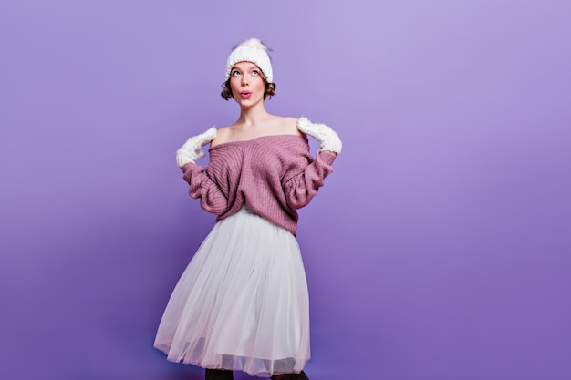 Signora spensierata in guanti di lana in posa con l'espressione del viso sognante. ritratto dell'interno di giovane donna in cappello lavorato a maglia e gonna lunga bianca isolata sulla parete viola.