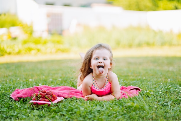 Carefree little girl lie on the grass with plate of fresh ripe strawberries and show her tongue. childhood, fun, happiness.