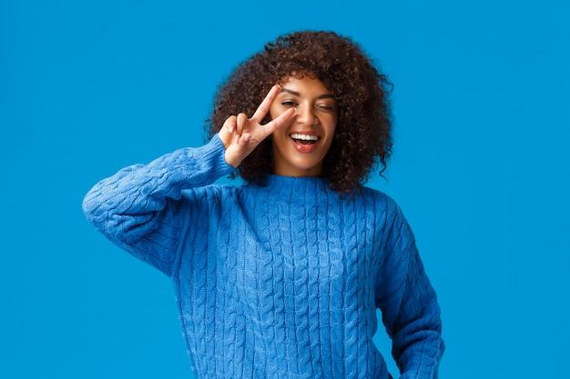 Беззаботная милая, харизматичная афроамериканская женщина говорит, что cheeze позирует в восторге и приподнятом настроении, показывая знак мира подмигивающим глазом и улыбаясь, счастливо смеясь, наслаждайтесь зимними праздниками, синий
