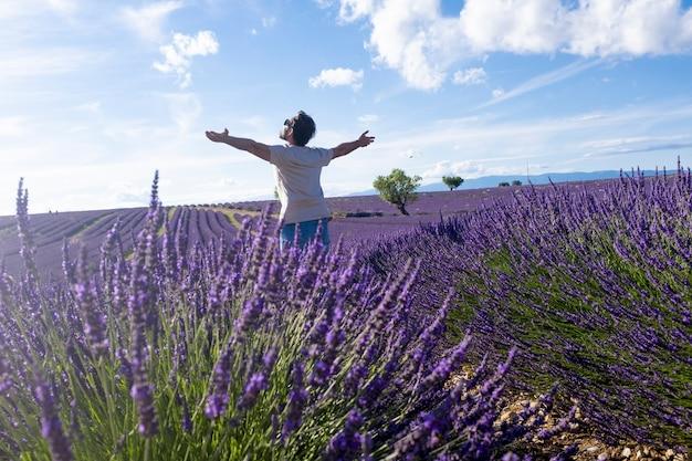 曇り空を背景にラベンダーの花畑に腕を広げて立っているのんきな男性観光客。美しいラベンダーの花畑で彼の自由を楽しんでいる男