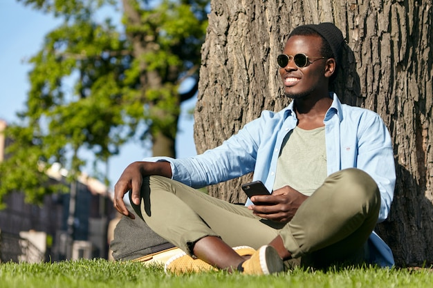 Carefree male with dark skin and white perfect teeth, wearing fashionable clothes, sitting at green grass of park, leaning at tree, holding mobile phone in hand, receiving messages from girlfriend