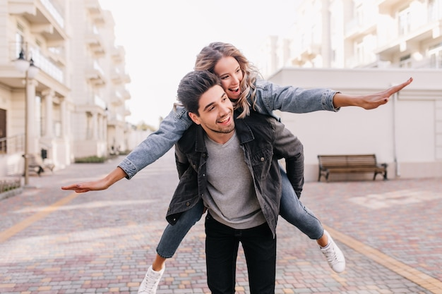 Carefree man in black jacket walking around with girl. outdoor portrait of blissful couple enjoying weekend together.