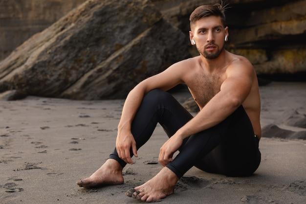 평온한 남자 챔피언은 맨발에 앉아 검은 색 레깅스를 입고 수염을 가지고 있습니다.