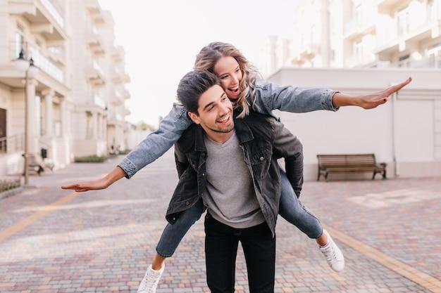 女の子と歩き回る黒いジャケットののんきな男。一緒に週末を楽しんでいる至福のカップルの屋外の肖像画。