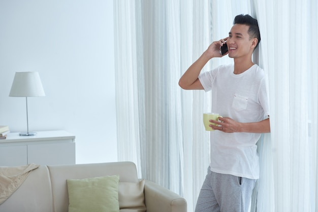 Carefree man with cup of tea leaning on his sitting room window while making a phone call