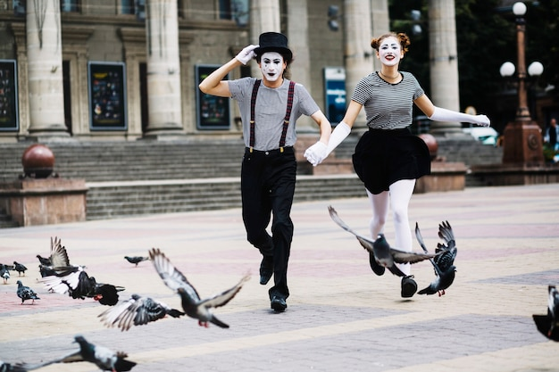 Carefree mime couple running on city street