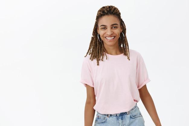 Беззаботная современная афро-американская девушка улыбается и выглядит счастливой