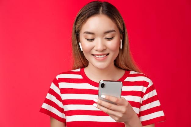 Carefree modern asian blond girl picking song wear wireless earphones listen music using online song...