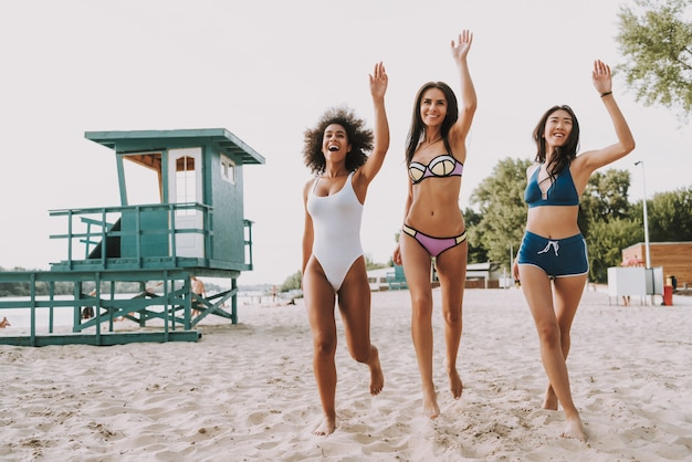 Carefree multiracial women run by sandy beach