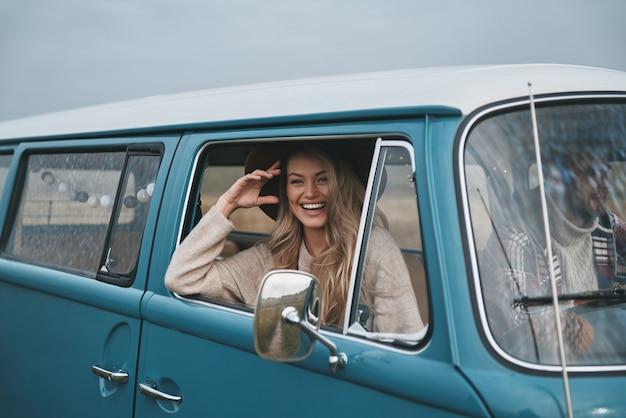 도로에서 평온한. 매력적인 젊은 여자가 밴을 바라보고 그녀의 남자 친구와 함께 자동차 여행을 즐기면서 웃고