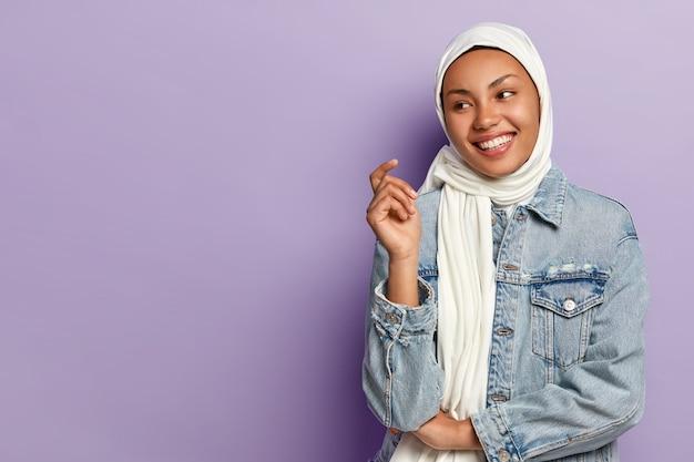 Donna spensierata e ottimista con un sorriso a trentadue denti, di buon umore, avvolta in una sciarpa bianca, indossa una giacca di jeans alla moda