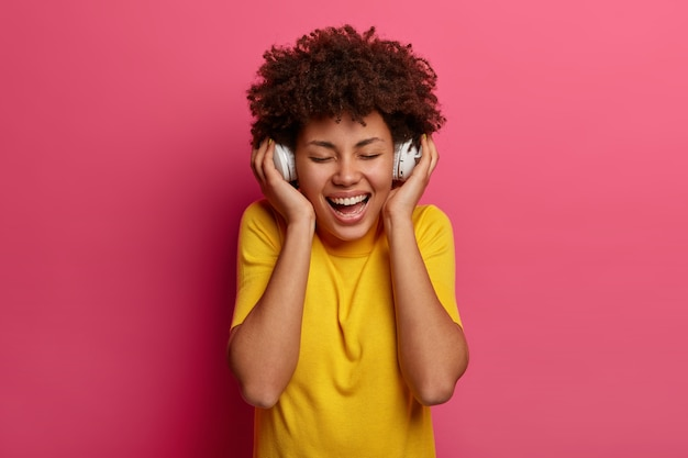 Carefree optimistic young woman smiles broadly, keeps eyes closed, shows white teeth, listens audio track, wears headphones on ears, enjoys every bit of new favourite song, laughs positively