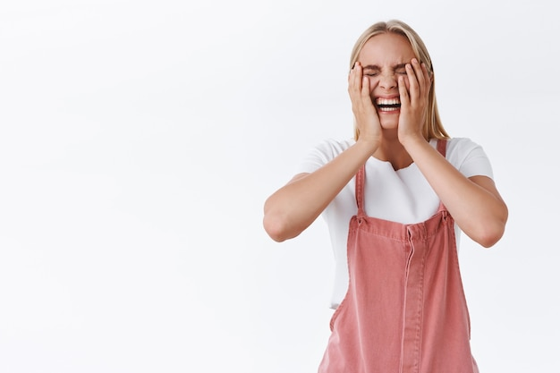 Carefree, outgoing good-looking caucasian blond woman in casual outfit, squeeze cheeks and laughing hard as watch funny comedy movie, having fun, fool around with friends, chuckling, white background