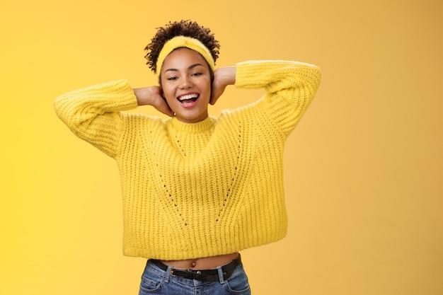 근심 없는 외향적인 젊은 아프리카계 미국인 소녀는 머리 뒤로 손을 뒤로 뻗어 편안한 스트레칭을 하며 게으름을 피우며 활짝 웃고 즐겁게 노란색 배경을 가지고 여가를 보냅니다.