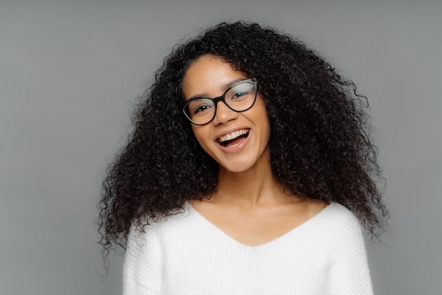 のんきな大喜びの黒い肌の女性は、元気で幸せに笑います