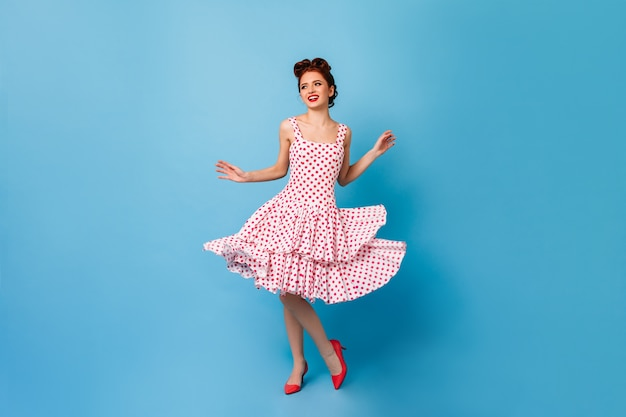 평온한 핀업 소녀 춤과 웃음. 푸른 공간에 재미 폴카 도트 드레스에 귀여운 젊은 여자.