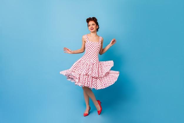 Ragazza pinup spensierata ballando e ridendo. giovane donna sveglia in vestito a pois divertendosi sullo spazio blu.