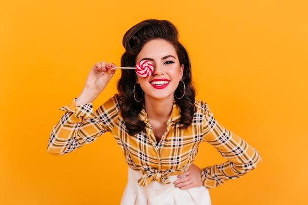 롤리팝을 들고 평온한 핀업 소녀. 노란색 배경에 재미 체크 무늬 셔츠에 웃는 우아한 여자의 스튜디오 샷.
