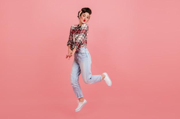 분홍색 배경에 점프 평온한 핀 업 소녀입니다. 청바지와 체크 무늬 셔츠에 사랑스러운 젊은 여자의 스튜디오 샷.