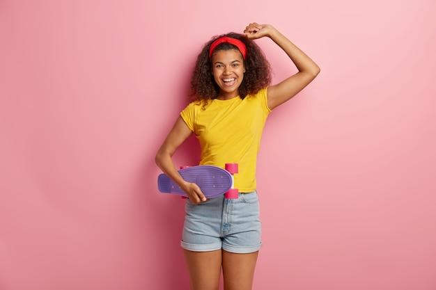 Беззаботная довольная темнокожая дама мастерски владеет трюками на скейтборде