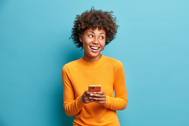 Carefree pleased female student uses mobile phone for online distant education looks gladfully aside and smiles broadly browses through internet during free time checks mailbox poses indoor