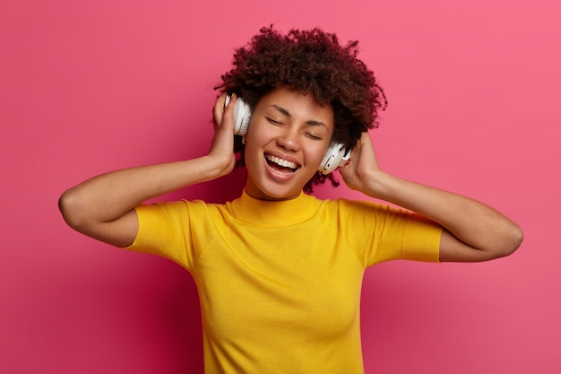 Carefree pleased millennial girl listens song in headphones, enjoys playlist, moves with rhythm, smiles broadly, keeps eyes shut, isolated on pink wall. people, leisure, lifestyle, hobby concept