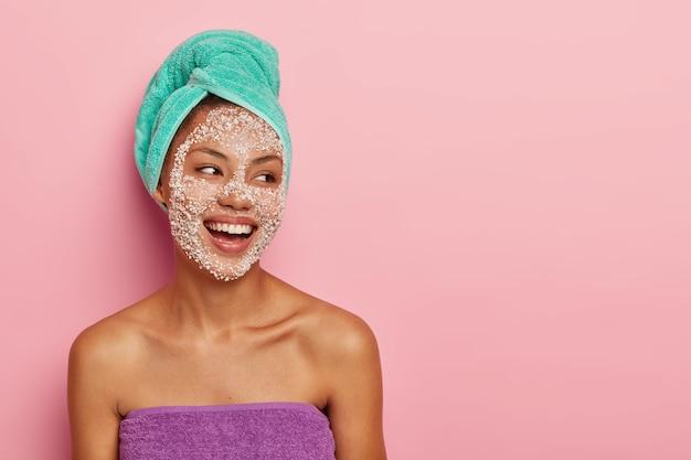 Spensierata donna soddisfatta con scrub viso, si preoccupa del benessere e dell'aspetto perfetto, avvolta in un asciugamano, concentrata da parte con un'espressione felice, ha un trattamento cosmico