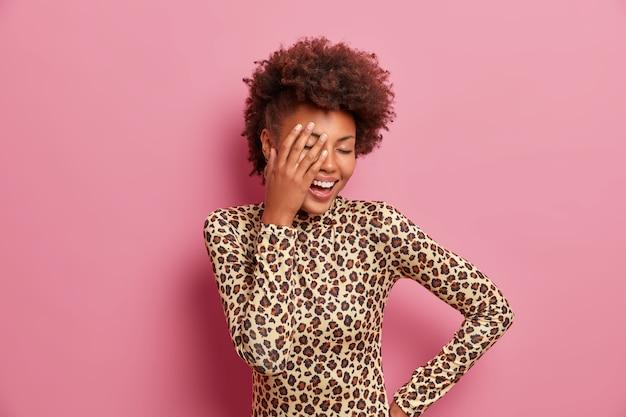 La spensierata donna afroamericana positiva fa il palmo della mano, ridacchia positivamente, tiene gli occhi chiusi, sorride a trentadue denti