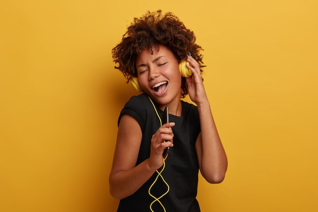 Carefree positive curly woman hears awesome track via headset, sings aloud with song, holds smartphone as microphone