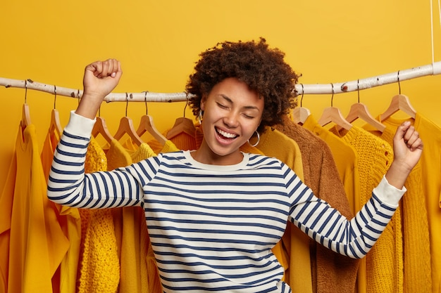 Carefree positive dark skinned woman dances happily, poses near clothes rack, rejoices day off and successful shopping, dressed in striped jumper
