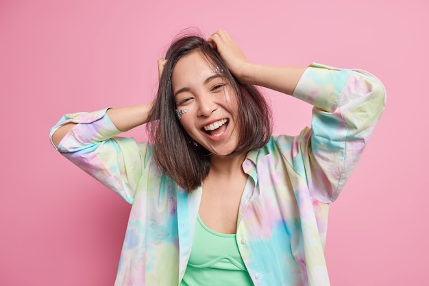 Carefree positive pretty asian teenage girl keeps hands on head moves actively enjoys life smiles broadly wears casual clothes feels amused has fun during spare time isolated over pink wall